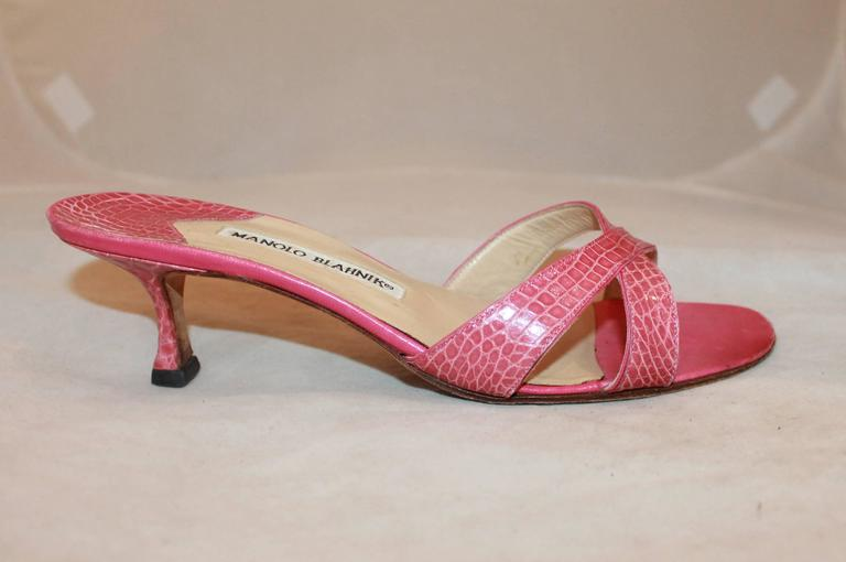 Manolo Blahnik Pink Crocodile Crisscross Slide with Heel - 38.5. These pink heels are slides with two straps crisscrossing on the top. They are in very good condition and show some wear on the bottom.