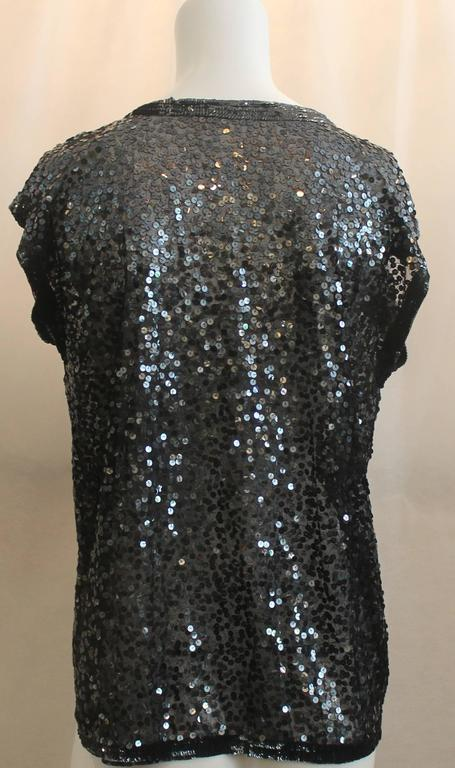 Zoran Black Sequin Short Sleeve Sweater - Medium. This sequined short sleeve sweater is completely covered in sequins. The trim is also sequined but the sequins are closer together. The fabric under the sequins is net-like and there is no closure.