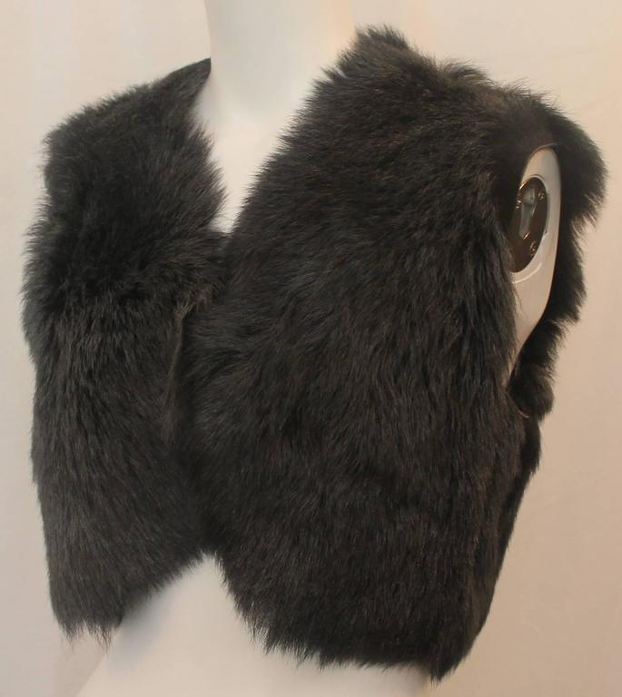 This Ralph Lauren black label grey shearling lamb vest is cropped and has one hook and eye closure in the front. Its lining is suede and the piece is in excellent condition with light wear consistent with use.