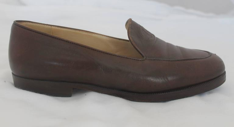 Chanel Brown Leather Loafers - 37. These brown loafers are made of leather and have the Chanel logo stitched into the top of the shoe. They are in good condition with minor wear on the inside and bottom. The front of each shoe show some