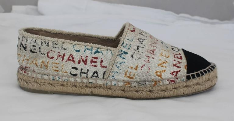 "Chanel Black and Cream with Multi-Colored Print Flat Espadrilles - 41. These espadrilles are great for the summer! They are cream with a black toe and tan, rope material stitching. The cream part of the shoe is covered with the word ""Chanel"" in"