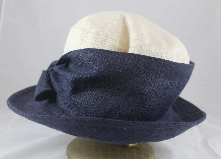Deborah Rhodes Collection  Ivory & Navy Canvas Hat with Front Tie. This hat is in very good condition with minor pulling on the top and sides. The light weight hat is great for spring and summer.  Brim- 3