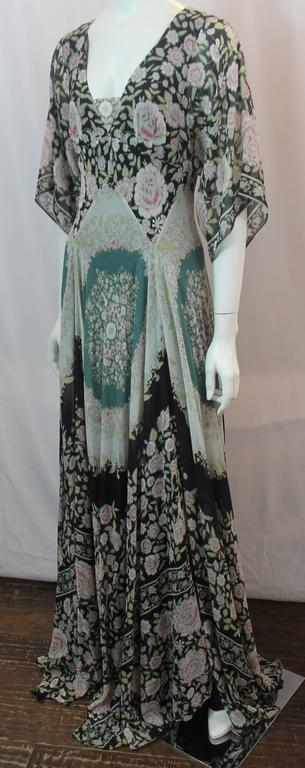 Etro Multi-Color Printed Silk Chiffon Peasant Style Gown - 44. This gown can double as a maxi dress and is floral printed with different colors such as black, light pink, and green. It has a peasant style and has elbow length sleeves, a back zipper,