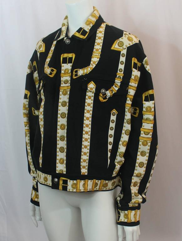 Versace Black, White & Gold Cotton Blend Studded Belt Print Jacket - 48. This 2000's jacket is in excellent condition with light wear consistent with age. The jacket has a jean material with a print that has black in the background and white