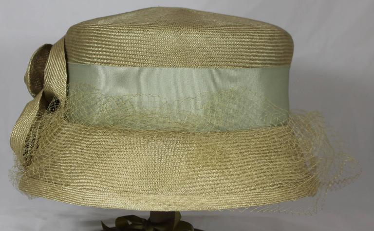 Suzanne Couture Millinery Light Olive Straw Hat with Ribbon, Flower, and Net. This hat is made of straw-like material. It is a light olive color and has a blueish green ribbon around it. There is a large light olive flower wit a button in the middle