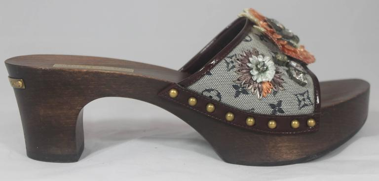 Louis Vuitton Grey Monogram Clog w/  Rhinestone and Floral Raffia Decor - 37. These unique clogs have a wooden look to them. On the back of the heel is a gold metal piece that says