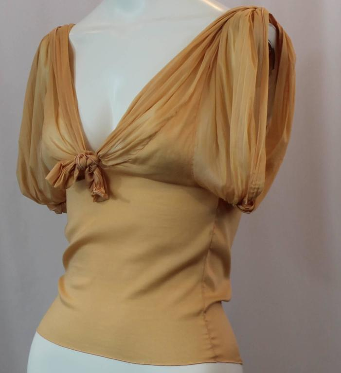 Christian Dior Mustard Colored Silk Ruched Sleeveless Blouse with Ties - S. This ruched sleeveless blouse has a front tie and a decorative back tie/ decoration. There is a plunging neckline and the blouse is made of a stretchy silk material. It is