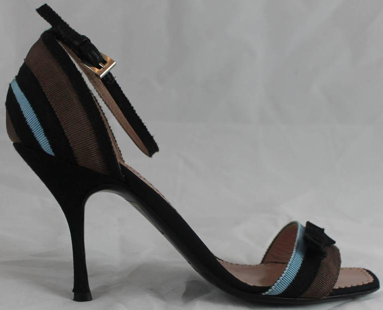 Prada Blue, Black, and Brown Grosgrain Striped Heels with Ankle Strap and Bow-36. These shoes are black with a blue, black, and brown striped grosgrain band with a small black bow. The heel is thin and these shoes come with a duster. They are in