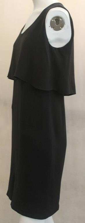 Chanel Black Silk Sleeveless Dress - 36 - 07A. This classic dress is has a flowing style with the upper portion near the bodice having one piece of hanging fabric. It is in excellent condition.