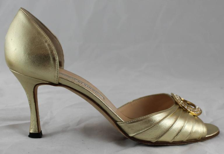 Manolo Blahnik Gold D'Orsay Heels with Rhinestone Detail - 36.5. These heels are a shiny gold color with an open toe. The front band has pleating and a rhinestone detail. They are in very good condition with minor sole wear and minor wear to the
