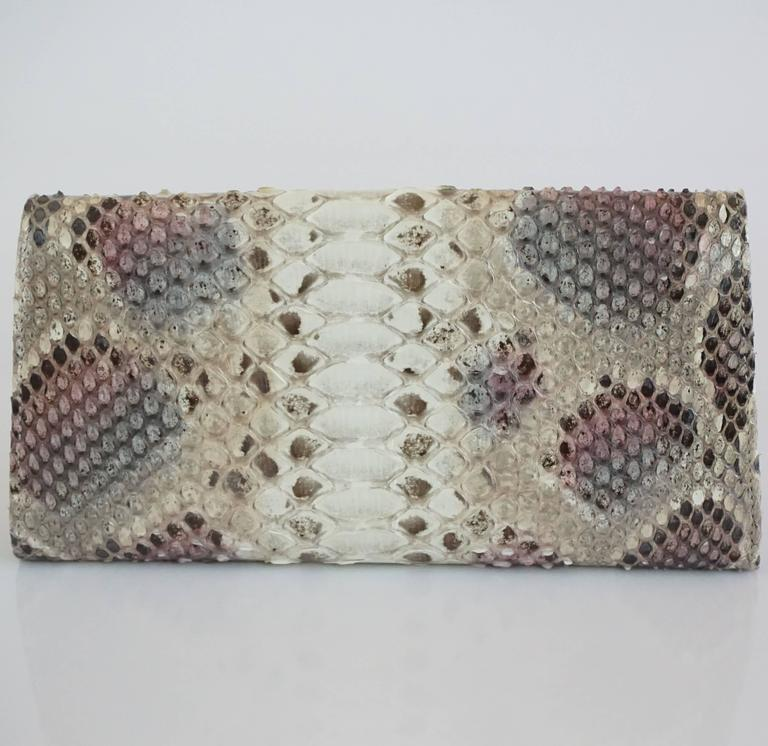 Jimmy Choo Earthtone Python Clutch with Strap - GHW. This clutch is an elegant piece which features a light gold closure with the Jimmy Choo logo, a leather and grosgrain interior, 8 card slots, 1 large zipper compartment, and a strap with chain