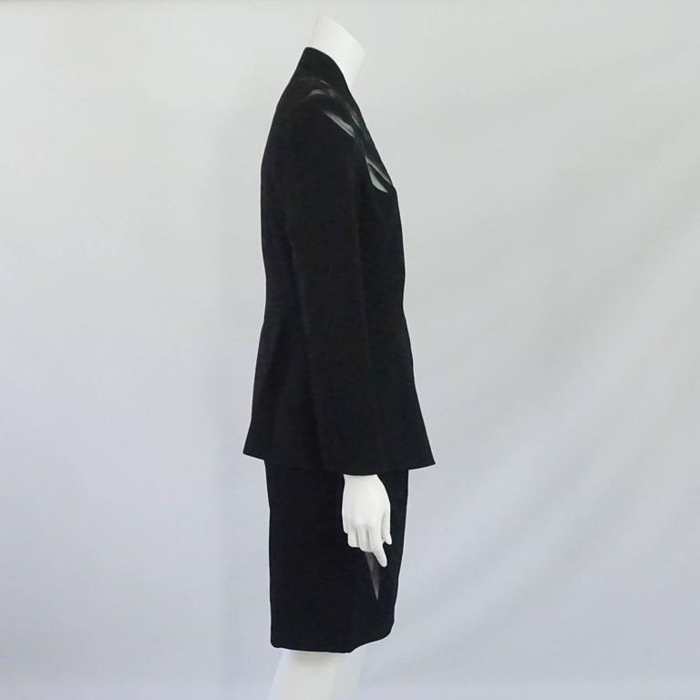 Thierry Mugler Black Wool Skirt Suit with Mesh Cutout Design - 42 - 1980's. This single breasted jacket is fitted to the waist with a slight flare outwards and a mesh detail all along the shoulders down to the bust. The jacket also has button