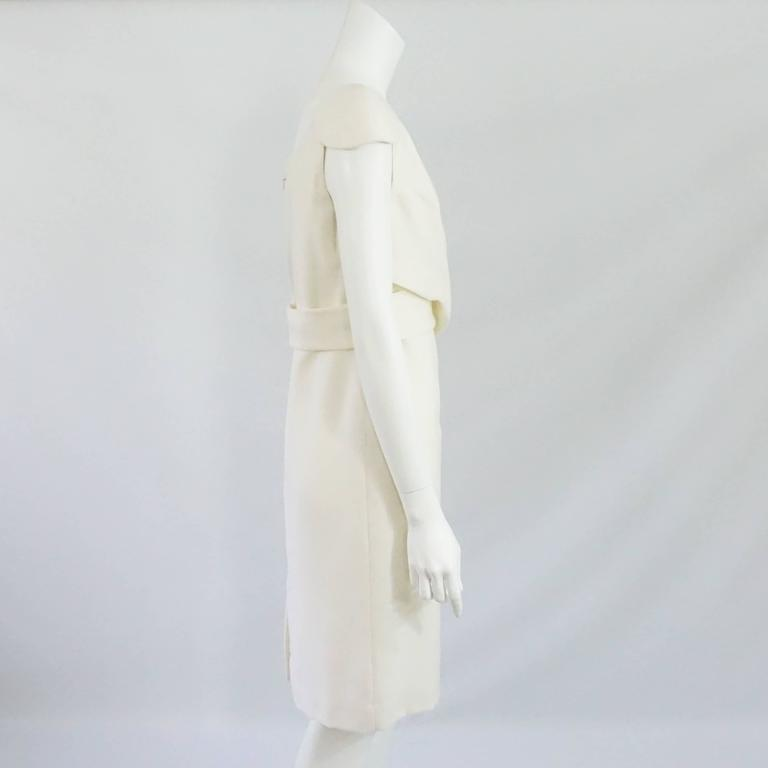 Alexander McQueen Ivory Wool Dress with Crossed Front Design - 46. This dress is a classic must have. It features a padded cap sleeve, V-neck, back zipper, back center slit, and crossing fabric in the bust to waist area. It is in excellent condition