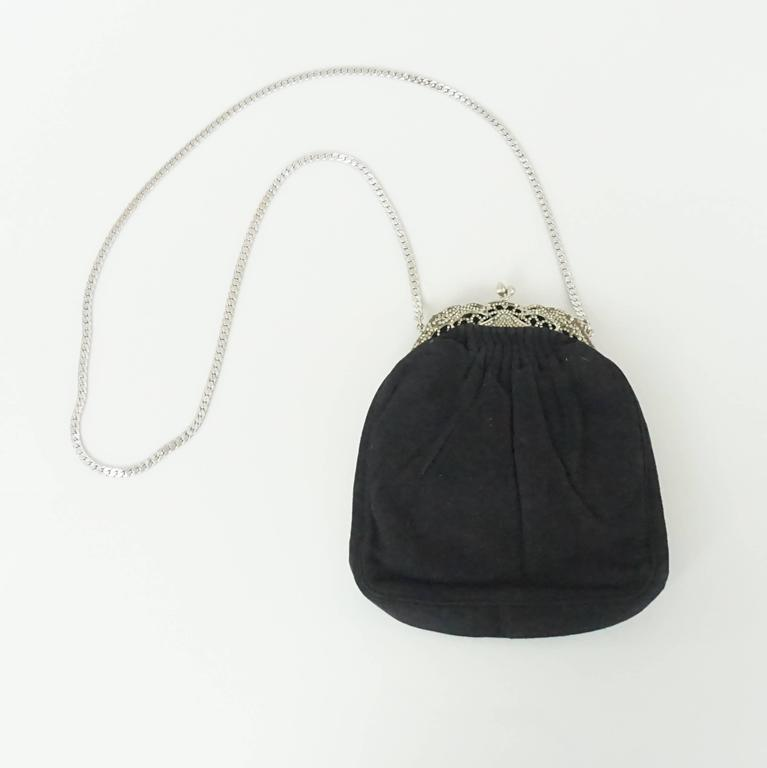 Judith Leiber Black Suede Rhinestone Evening Bag. This beautiful piece mixes new with vintage trends. It is in fair vintage condition with some wear to the suede and rhinestones on the top being missing. The bag has a black satin lining and a silver