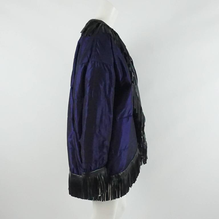 YSL Blue Puffer Coat with Black Fringe Trim - 40 - 1980's. This piece is truly spectacular and a great way to spice up a winter outfit. The jacket is has a blue-purple hue with a slight sheen. It features a leather fringe trim, shoulder pads, and an