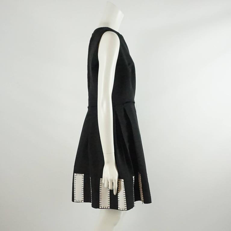 This Oscar de la Renta dress is black and has white grosgrain rectagular detailing with black stitching on the bottom of the skirt. The top is sleeveless and the skirt portion has pleats. The dress is in excellent condition.  Measurements Bust: