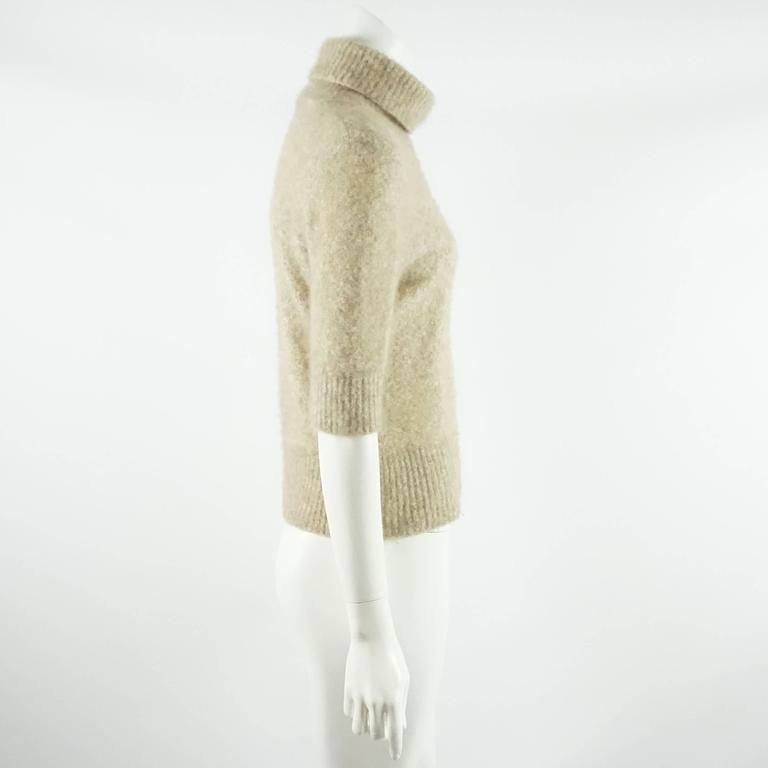 This beautiful beige Loro Piana turtleneck is a soft cashmere. The sleeves on this sweater are around elbow length. It is in good condition with some pilling.  Measurement Bust: 36