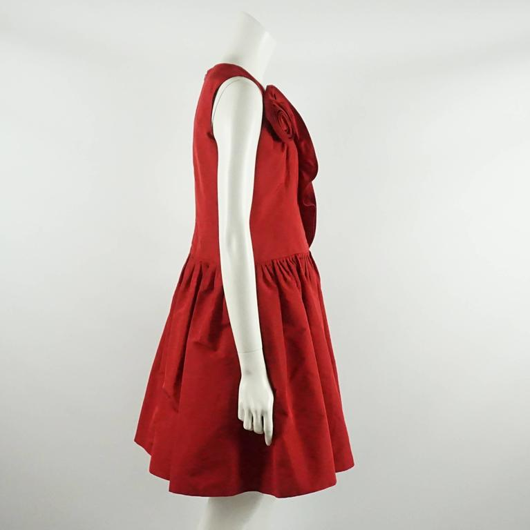 This Oscar de la Renta red silk taffeta dress is sleeveless with a drop waist and pleating at the beginning of the skirt. This dress also has a ruffle that leads into a rose along the bodice and going up to the bust. This dress is in excellent
