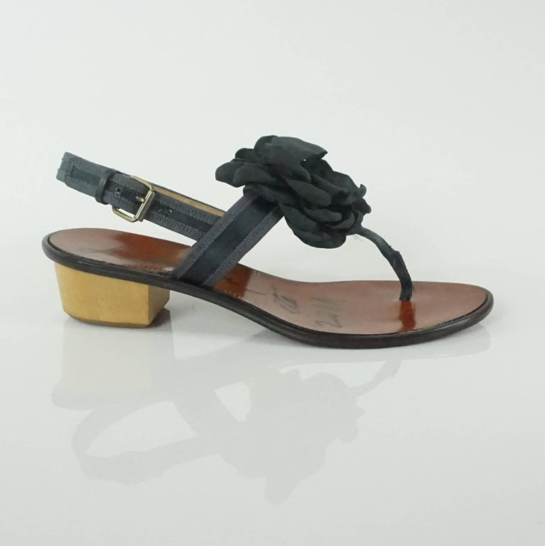 These Lanvin black satin sandals have a dark grey trim and a large silk camellia in front. The heels are wooden and the sandals are in good condition with some wear on the bottom and front. These shoes come with a duster and box.