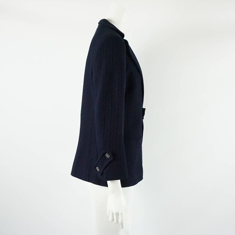 "This Chanel navy cotton jacket has an open style with a strip of fabric in the center acting as a closure. It has silver and navy enamel buttons with center ""CC""s on the center and cuffs. The fabric is textured and there are two front pockets. The"