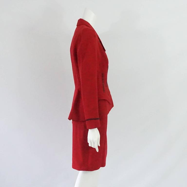 This Thierry Mugler red wool skirt suit has rhinestone detailing on the front and cuffs. There are 2 angular pockets on the front, a collar, and shoulder pads. This skirt suit is in very good condition.  Jacket Measurements Shoulder to