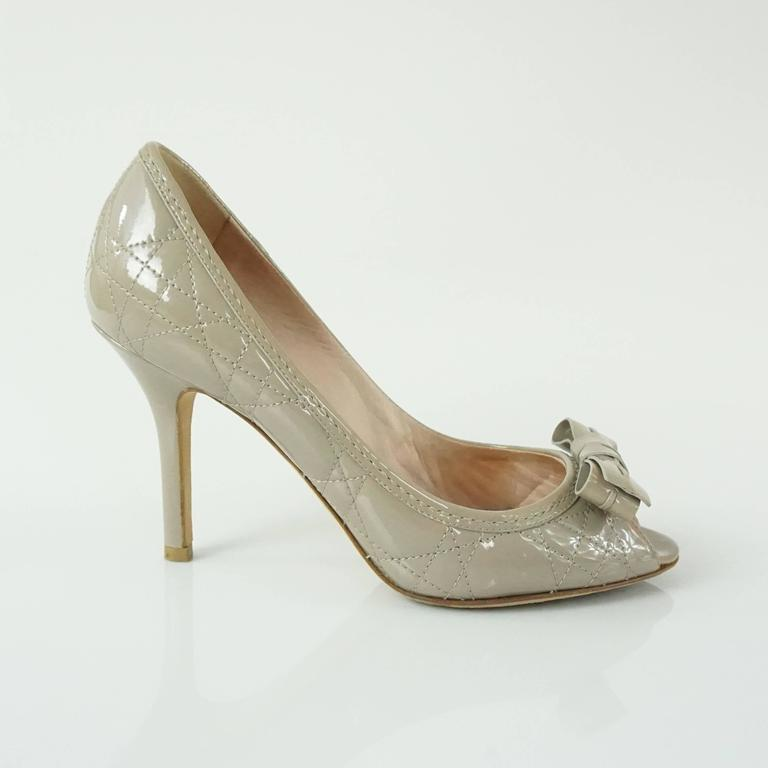 These Christian Dior quilted patent heels have a peep toe. They are taupe and have a bow by the toe. They come with a duster and are in very good condition with some wear on the bottom and some very minor wear on the leather.