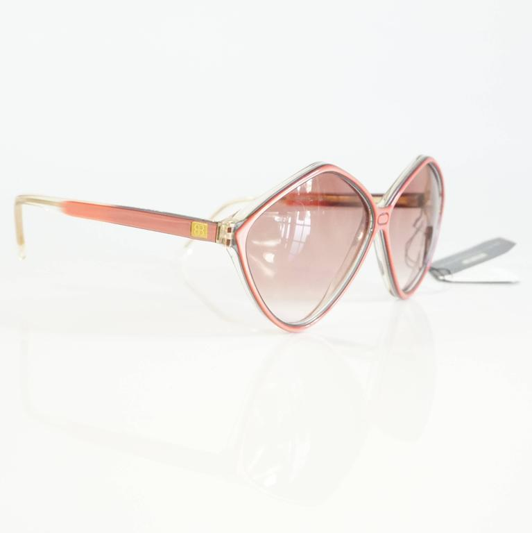 """These unique Balenciaga sunglasses are pink and lucite with a diamond shape. They come with the original tags. They are in excellent condition. Circa 1970's.   Measurements Leg Length: 5"""" Front (lens to lens): 5.7"""" Lens Height:"""