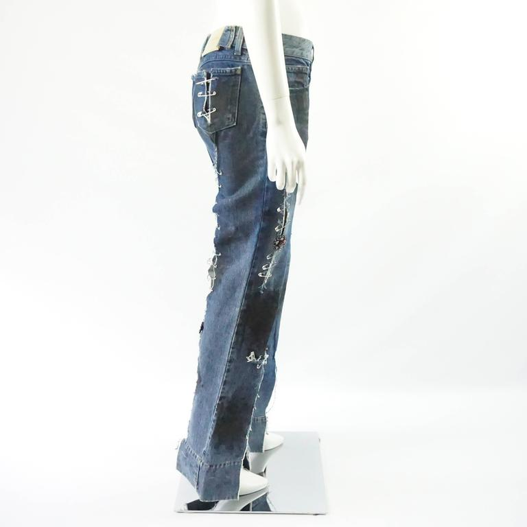 These very unique Dolce & Gabbana grunge jeans have a flared leg and are highly distressed. They have black splashes all over and slits on the thighs, bottom of the leg, back pockets, and on the back of the legs. One of the splashes is in the shape