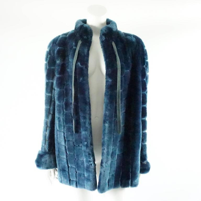This vintage Dior blue faux fur coat has 2 front ties and hook and eye closures. The coat has square fur sections with suede in between. This coat is in fair vintage condition with some staining on the suede and some of the lining by the armpit is
