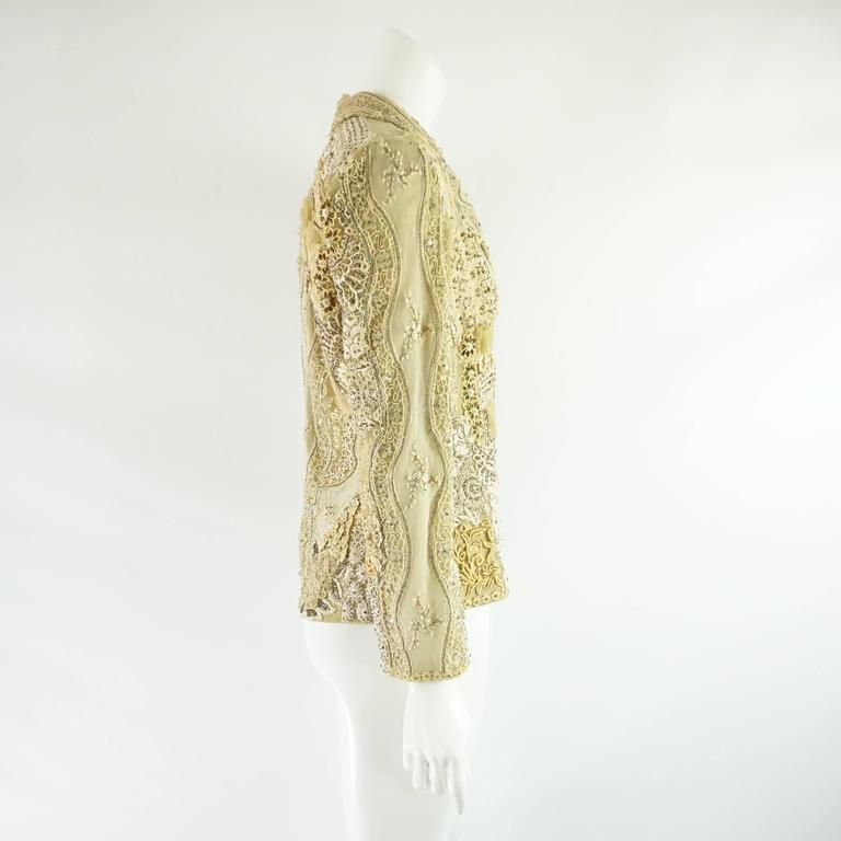 This stunning Ella Singh jacket is covered with different types of lace and embroidery with rhinestone strips and detailing. The jacket has a collar, shoulder pads, and iridescent buttons. The piece is in good vintage condition with some snags and