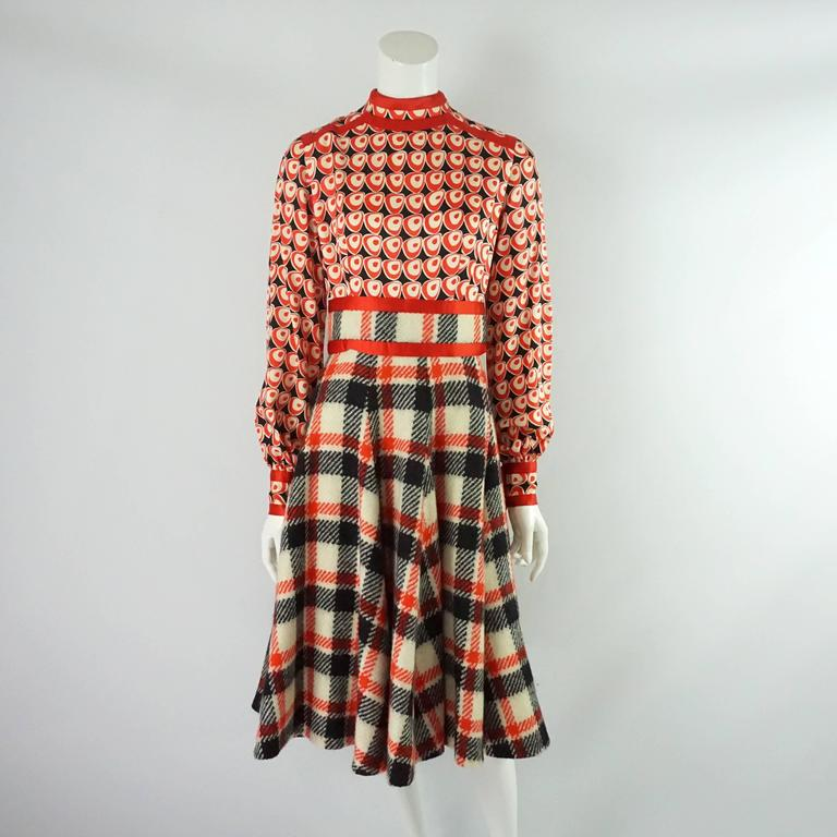 This classic yet funky Ronald Amey set comes with a long sleeve dress and jacket. The dress' bodice is a silk geometric print with a wool plaid skirt and red silk trim; it also has pockets in the front. The jacket is also a plaid wool with the red