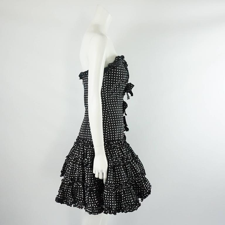 This Oscar de la Renta strapless dress is a polka dot silk taffeta fabric. The dress has a ruffle trim all over, 3 bows on the front, inside boning, and a back zipper. It is in excellent condition with light wear. Size 8.