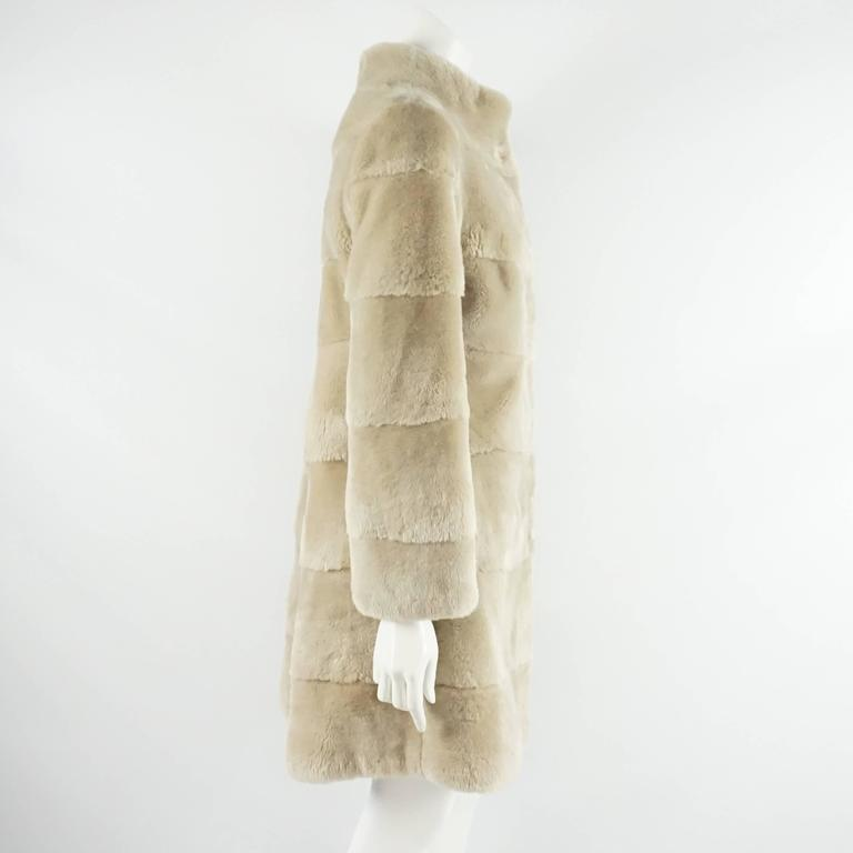 "This Olivia Preckel ""Noa"" coat is cream sheared beaver. It features a high neck and front closures. This coat is in excellent condition.  Measurements Shoulder to Shoulder: 16"