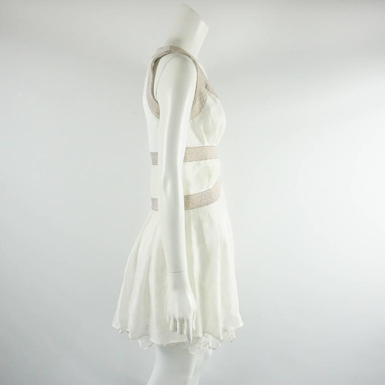 This Nina Ricci ivory dress has a thick lace underpinning with a sheer cotton overlay. The dress also has a copper metallic stitched design along the bodice, flowy style, and a side zipper. The dress is in very good vintage condition with light wear