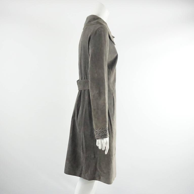 This Fendi dark grey full coat is made of suede and has sequin designs on the cuffs and center closure. The coat also has a collared neck, 2 front pockets, a belt piece in the back, and snap buttons. It is in excellent vintage condition with one