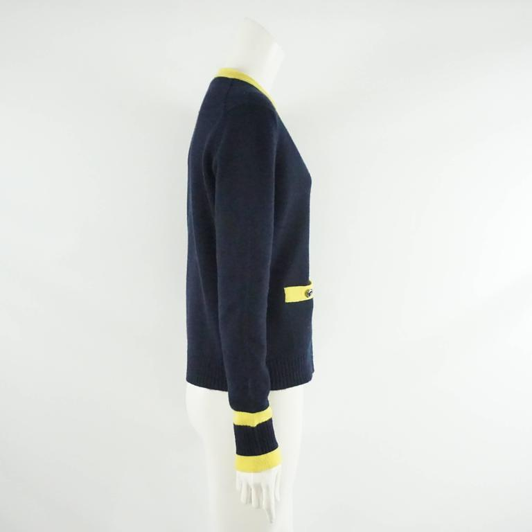 This Chanel cashmere sweater is navy with a yellow trim. The buttons are a dark gray and there are 2 pockets on the front. At the bottom of the sleeves there are 2 yellow stripes. This sweater is in very good condition with minor