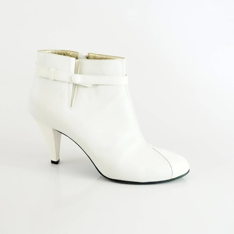 "These Chanel white lambskin and patent leather booties are a modern staple. They have a side fold, ankle strap with ""CC"" logo, inside zipper, and patent cap toe. The inside lining is gold leather and the heels are also patent. The boots are in fair"