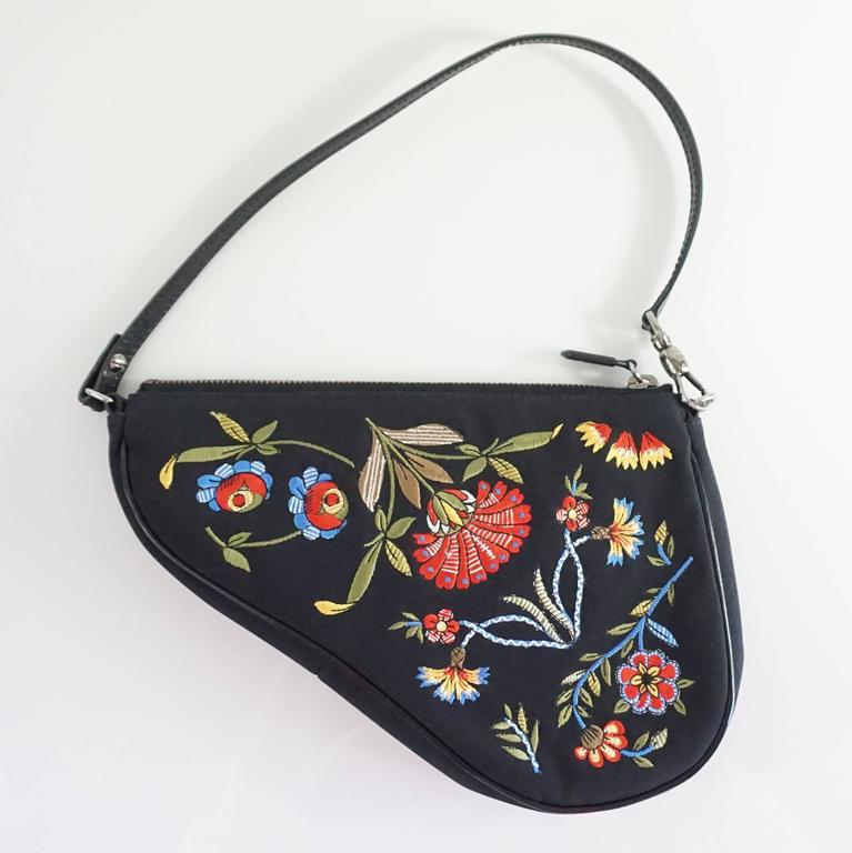 16db5a17f4 This unique Christian Dior saddle bag is black with a multicolored embroidered  floral design. It