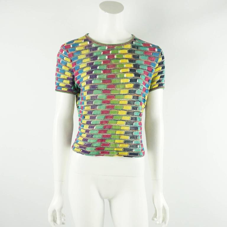 This vintage Missoni sweater set has a multi colored pattern on both the top and the sweater. The sweater has long sleeves and clear lucite buttons. The top has short sleeves and a rounded neckline. Both pieces are in excellent vintage
