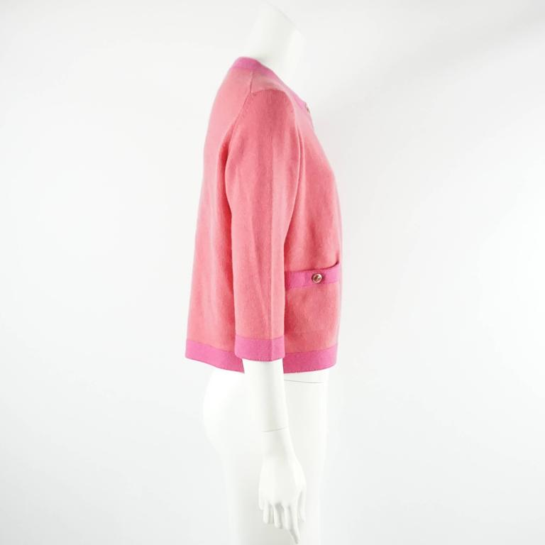 This Chanel cashmere sweater is salmon colored with a pink trim and is from the 2007P collection. There are 2 pockets on the front of the cardigan with  gold and pink Chanel logo buttons and a single top button for closure. This sweater is in