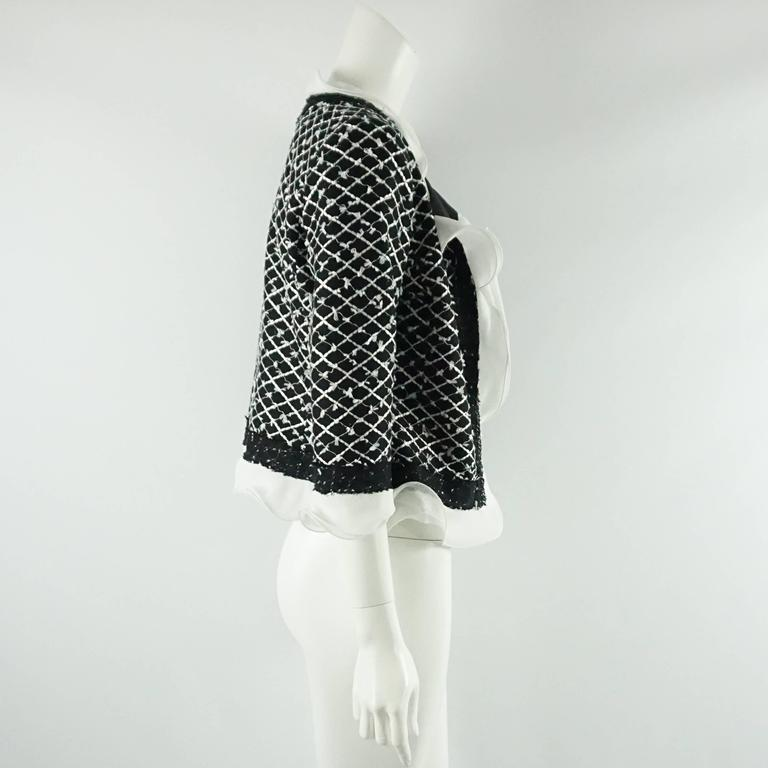This Oscar de la Renta black and white tweed jacket is a classic staple. It has a fringe and silk chiffon ruffle trim all around with no closure in the front. The fabric is a cotton-synthetic blend with silk lining. There are also very thin shoulder