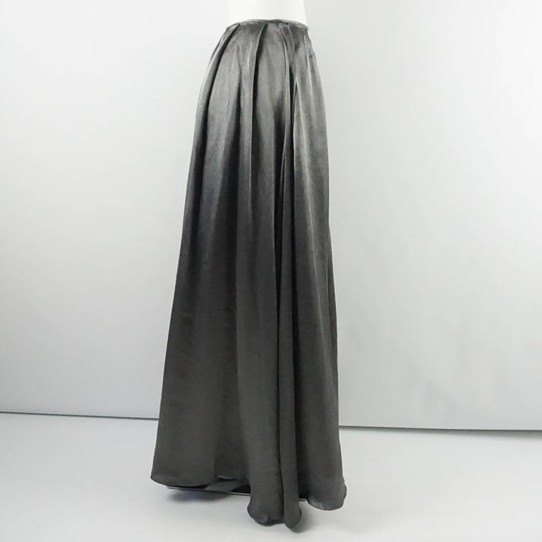 This Valentino maxi skirt is a show stopper. It falls at the waist with large pleats cascading down and it is lined with an acetate shell. The skirt is in good condition with some general fabric wear and a couple areas with small pulls as seen in
