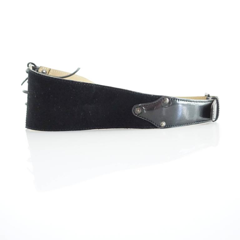 This Alaia belt is suede with a patent leather front. It has a angular look and lace-up front closure. The piece is in fair condition with some wear to the laces, belt strap, and interior as seen in the images. Additionally the belt looks somewhat