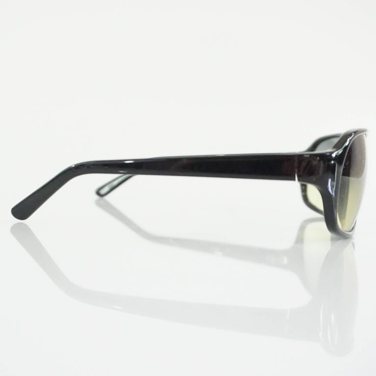 """These Prada sunglasses have a black frame and feature yellow tinted rectangular lenses. These sunglasses are in excellent condition.  Measurements Front Length: 5.88"""" Leg Length: 5"""" Length of Lens: about 2.5"""" Height of Lens: 1.75"""""""