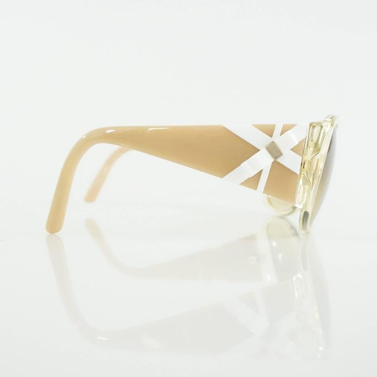 "These Versace sunglasses are beige with tan lenses. On the sides are white detailing and a white bow with gold detailing. These sunglasses are in excellent condition.  Measurements Front Length: 5.5"" Leg Length: 4.75"" Length of Lens:"