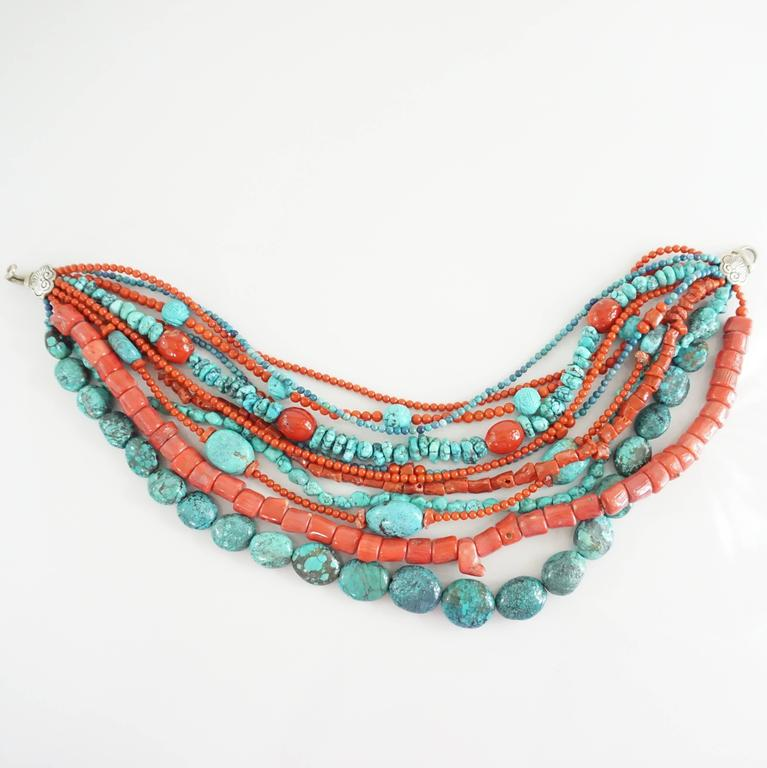 "This Stephen Dweck necklace has 11 strands of turquoise and coral. It has a silver closure and different size and shaped beads. This necklace is in excellent condition.   Measurements Length: 17"" Width: 2""- 4"""