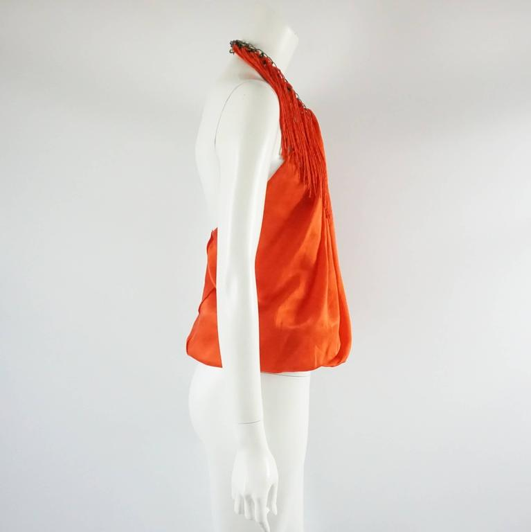"""This Lanvin bright orange silk halter top has a chain by the neckline with hanging fringe tassels. The top is in good condition with a couple minor markings as shown in the last images. Size 38.   Measurements Bust: 35"""" Waist:"""