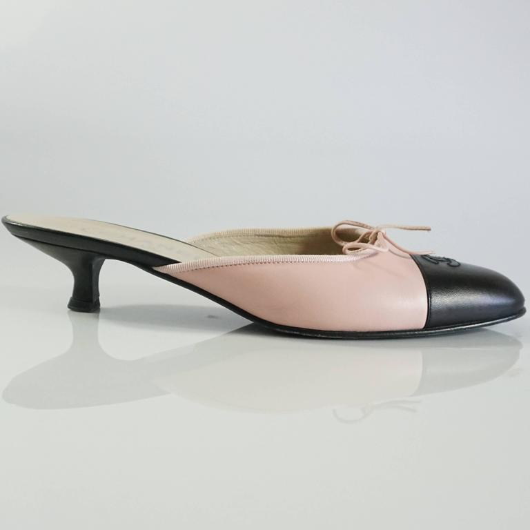 These Chanel slides have a low black heel and are pink with a black cap toe. They feature a pink bow and the Chanel logo on the black. These shoes are in very good condition with some bottom wear, markings, and a scuff on the leather. Size 40.  Heel