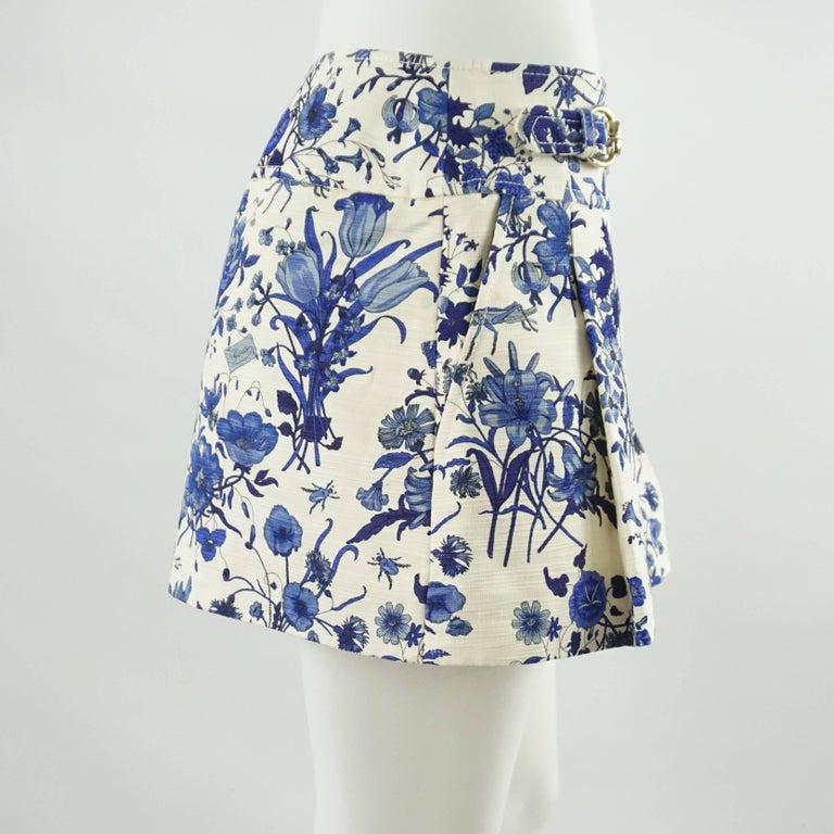 This Gucci mini skirt is ivory cotton with a blue floral print. It features: front pleats, two pockets, and two silver buckle detailing. There is a matching bathing suit available for purchase. This skirt is in excellent condition. Size