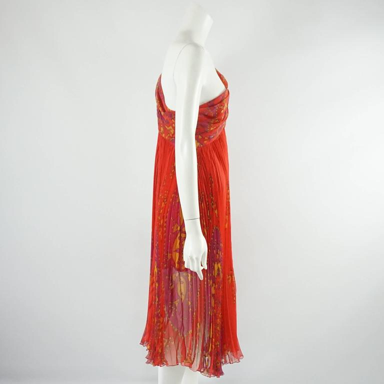 This fabulous Christian Dior cocktail dress is red with a floral-esque print on it. The dress is made of silk chiffon with a pleated skirt and ruched along the bust and single strap. The side zipper also has button detailing along the sides. The